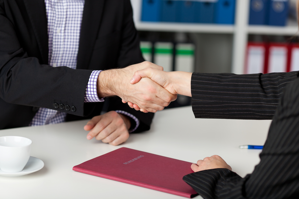 Businessman and businesswoman shaking hands at office desk